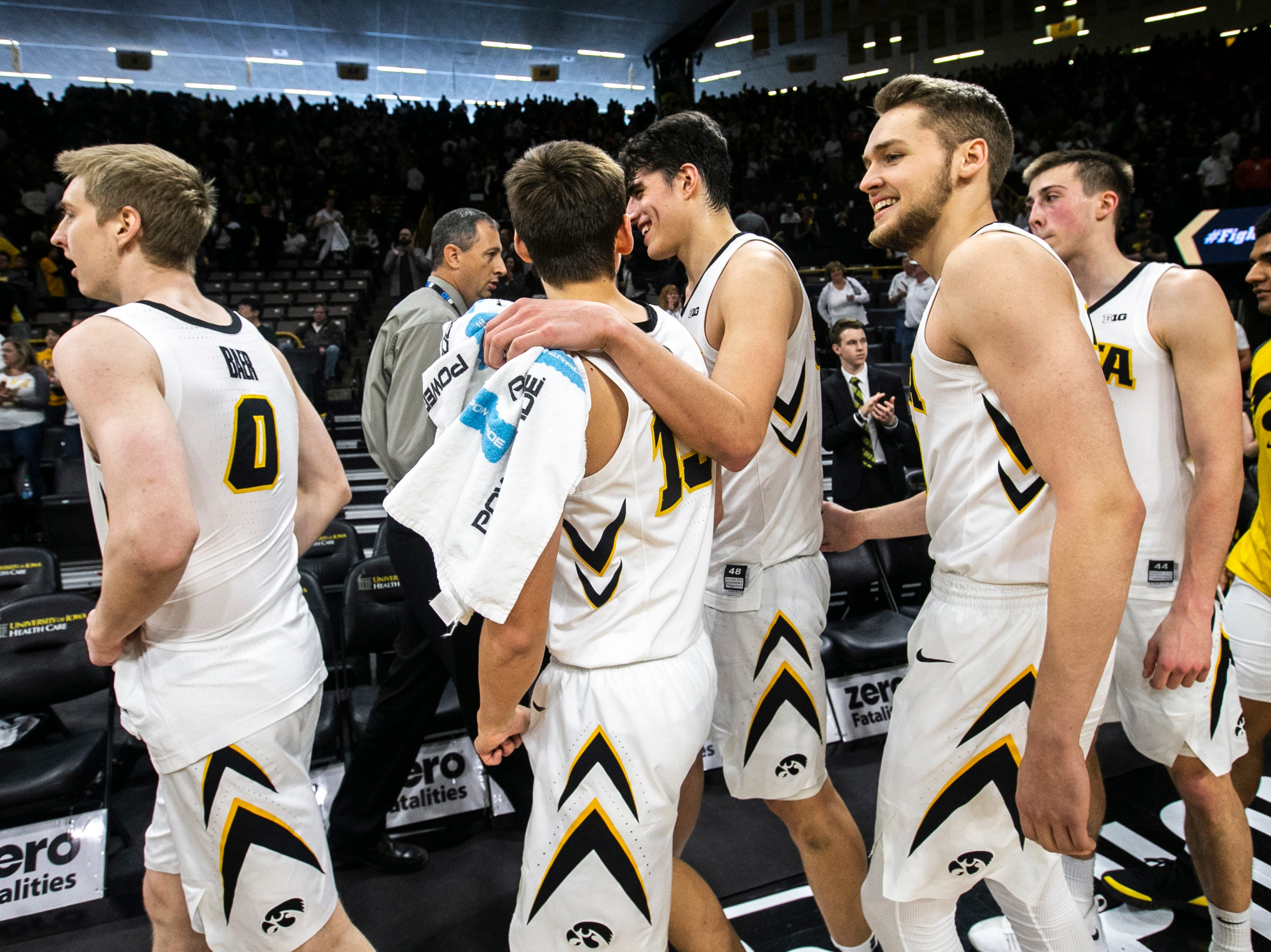 Iowa forward Luka Garza (55) talks with Iowa guard Austin Ash (13) after a NCAA Big Ten Conference men's basketball game on Sunday, Jan. 20, 2019, at Carver-Hawkeye Arena in Iowa City, Iowa.