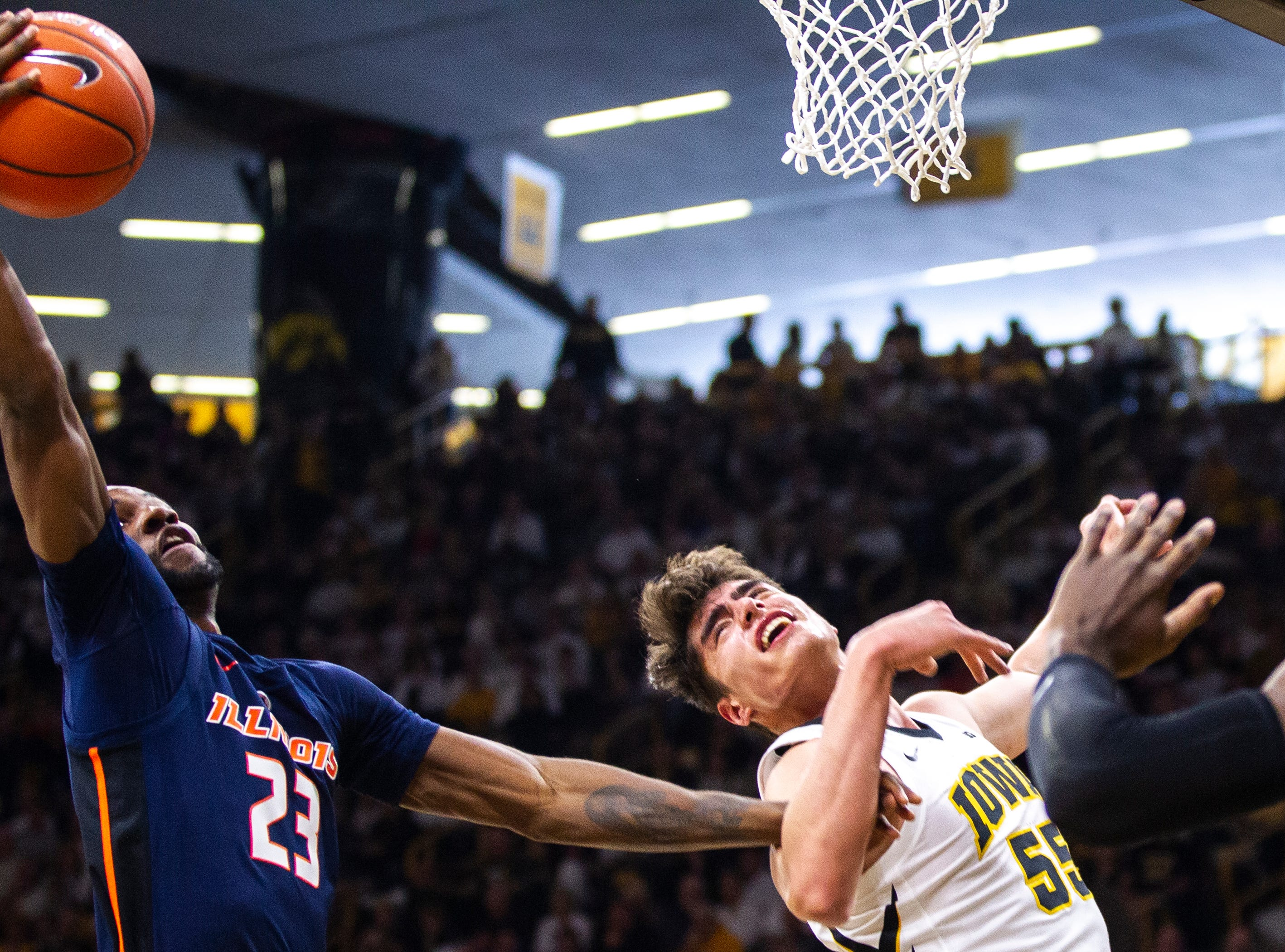 Illinois' Aaron Jordan (23) pulls in a rebound past Iowa forward Luka Garza (55) during a NCAA Big Ten Conference men's basketball game on Sunday, Jan. 20, 2019, at Carver-Hawkeye Arena in Iowa City, Iowa.