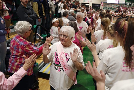 Cancer survivors high-five their supporters at the 11th annual Pink Out game at Triton Central High School on Friday, Jan. 18, 2019. The Pink Out game honors breast cancer survivors and supports the I.W.I.N. (Indiana Women in Need). Foundation.