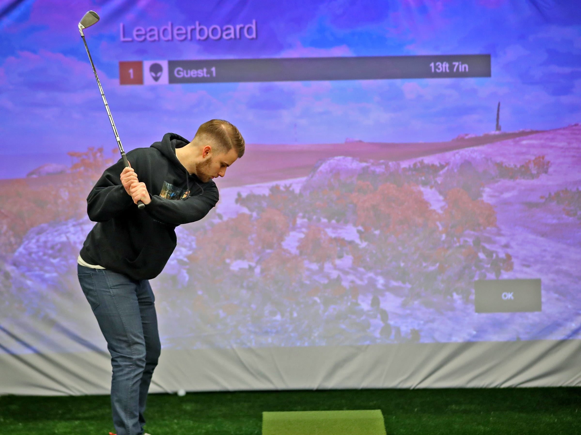 Elijah Prokopenko, with the Indy Golf Show, tries out the TruGolf simulator during the Indy Golf Expo at the Indiana State Fairgrounds, Sunday, Jan. 20, 2019.