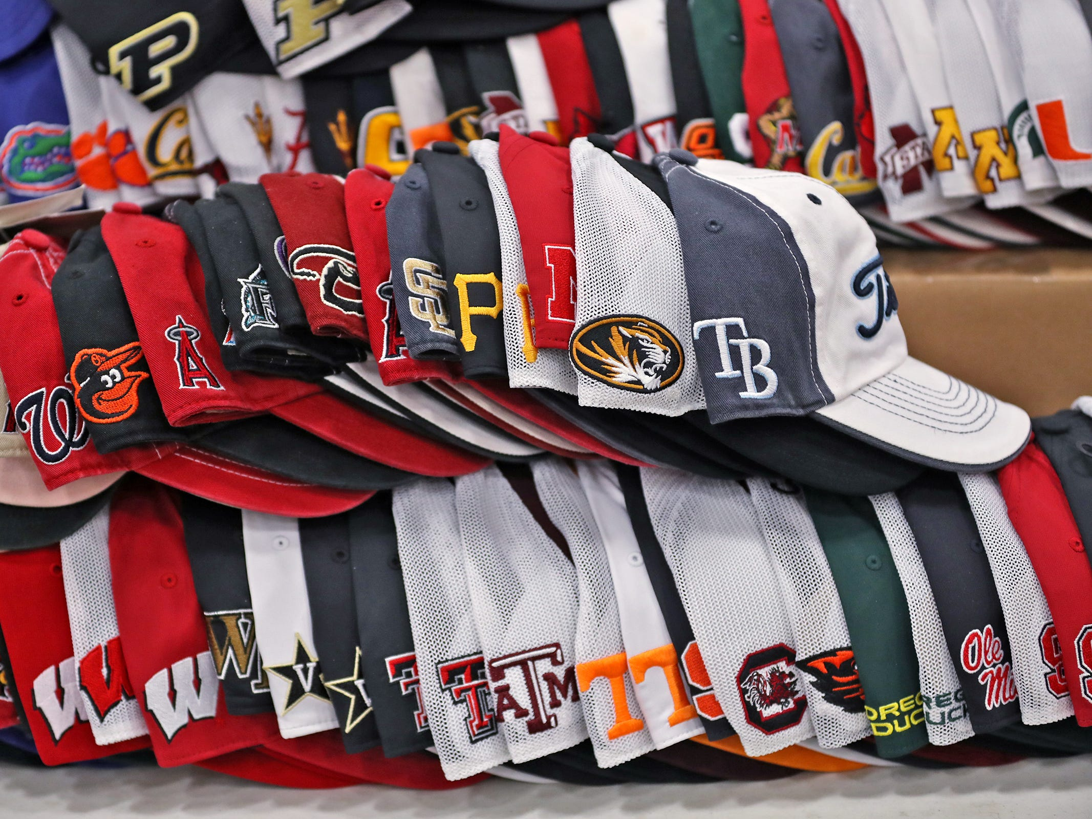 Hats with college logos are seen at the Golfmart Kentucky booth during the Indy Golf Expo at the Indiana State Fairgrounds, Sunday, Jan. 20, 2019.