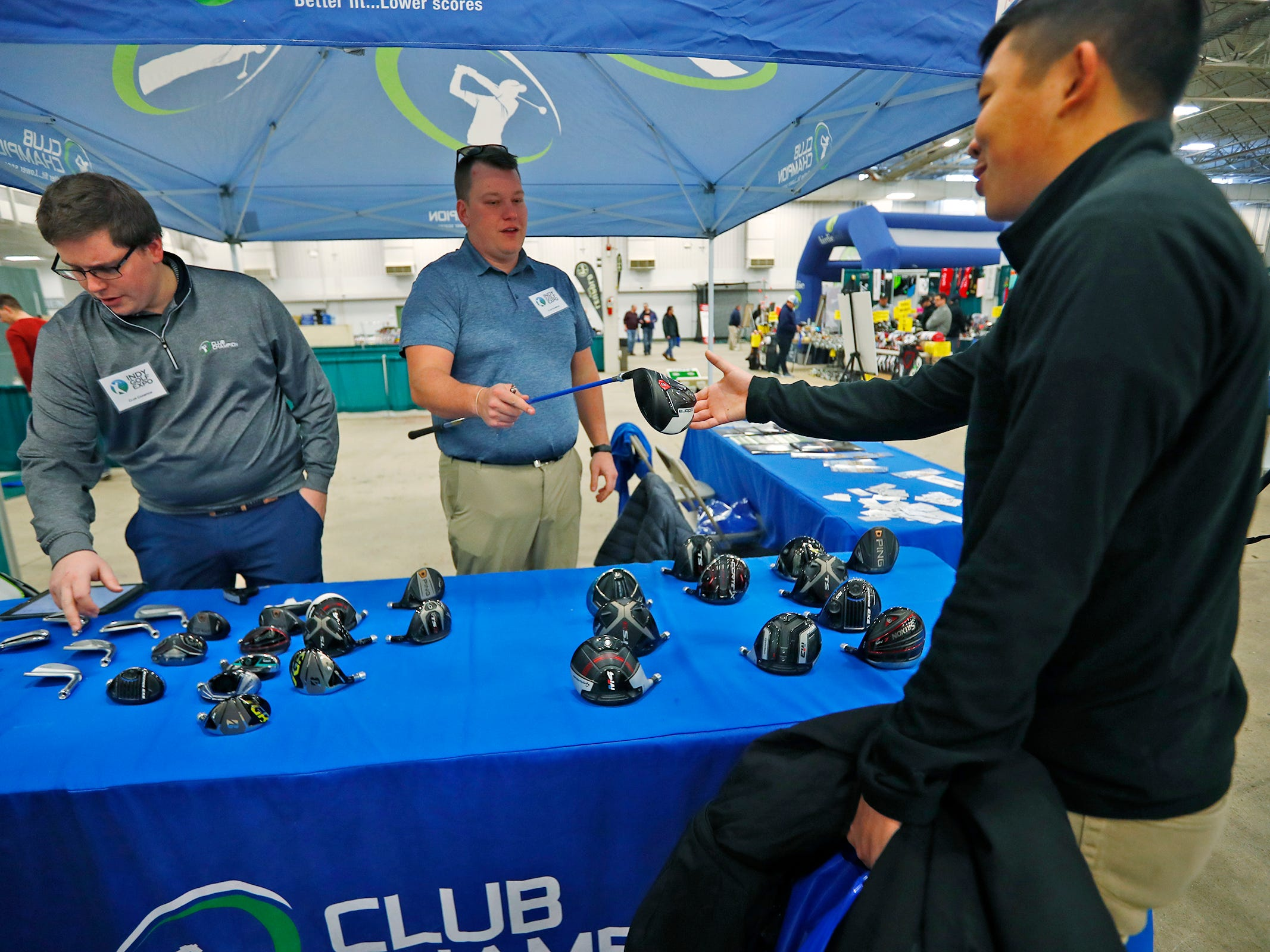 Scott Wong, right, gets a club to try out from store manager Joey Simon, center, at the Club Champion booth during the Indy Golf Expo at the Indiana State Fairgrounds, Sunday, Jan. 20, 2019.  Simon and Grant Gillard, left, are both Master Fitters and Builders at Club Champion.  The Indianapolis company does custom fitting with over 35,000 hittable combinations of clubs.