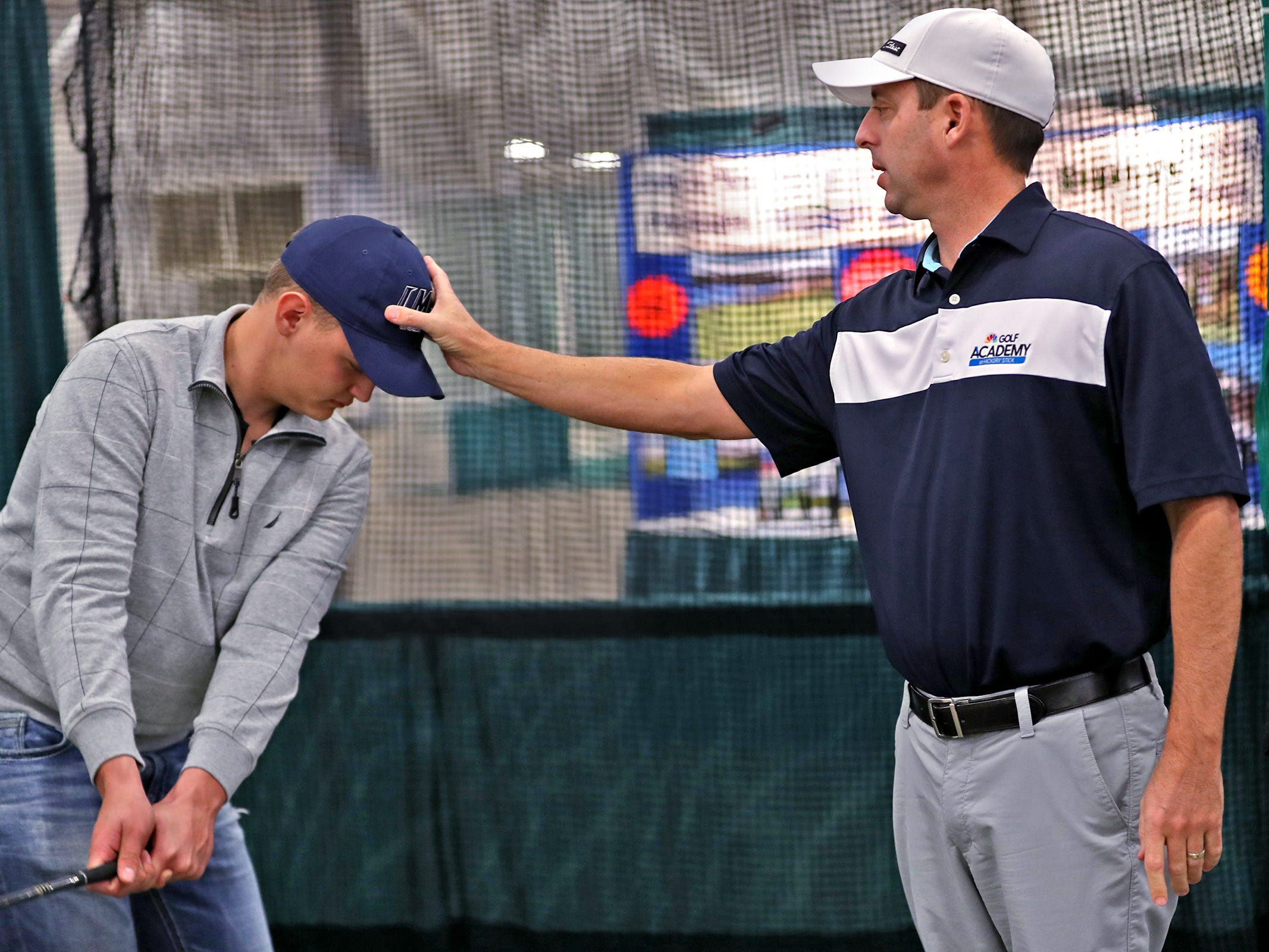 Brett Widner, left, gets tips about the positioning of his head during his golf swing, from Colby Huffman at the Golf Channel with Colby Huffman booth during the Indy Golf Expo at the Indiana State Fairgrounds, Sunday, Jan. 20, 2019.