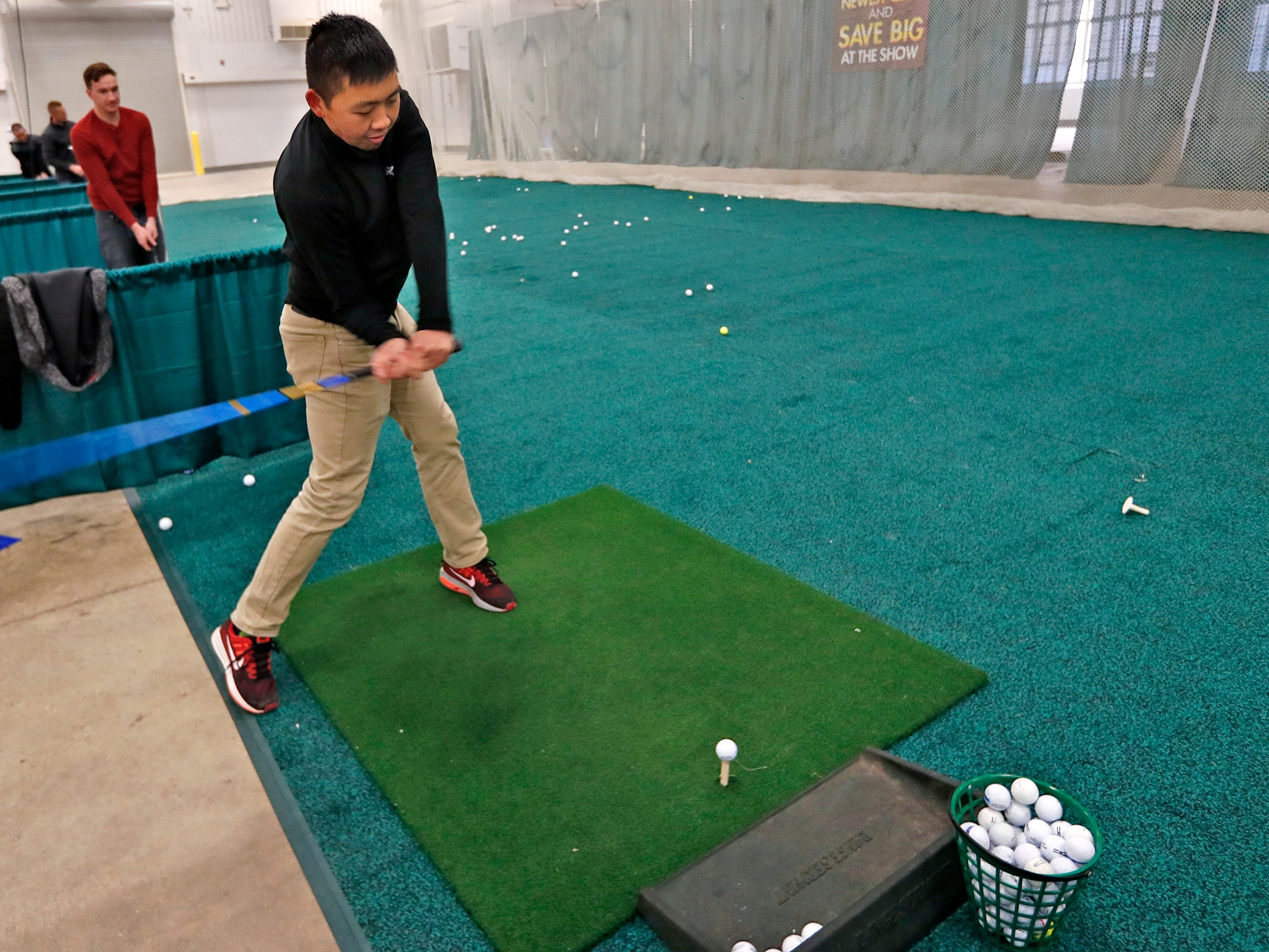 Sam Richmond, left, and Scott Wong try out clubs at the Club Champion booth during the Indy Golf Expo at the Indiana State Fairgrounds, Sunday, Jan. 20, 2019.