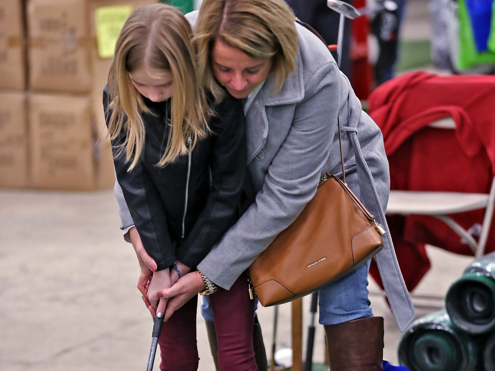 Harley Keller, left, gets help with her putting from Jennifer Carver at the Big Moss Golf booth during the Indy Golf Expo at the Indiana State Fairgrounds, Sunday, Jan. 20, 2019.