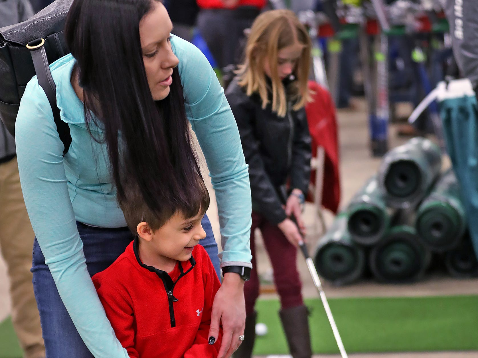 Abby Shafer helps her son Brody Shafer putt at the Big Moss Golf booth during the Indy Golf Expo at the Indiana State Fairgrounds, Sunday, Jan. 20, 2019.