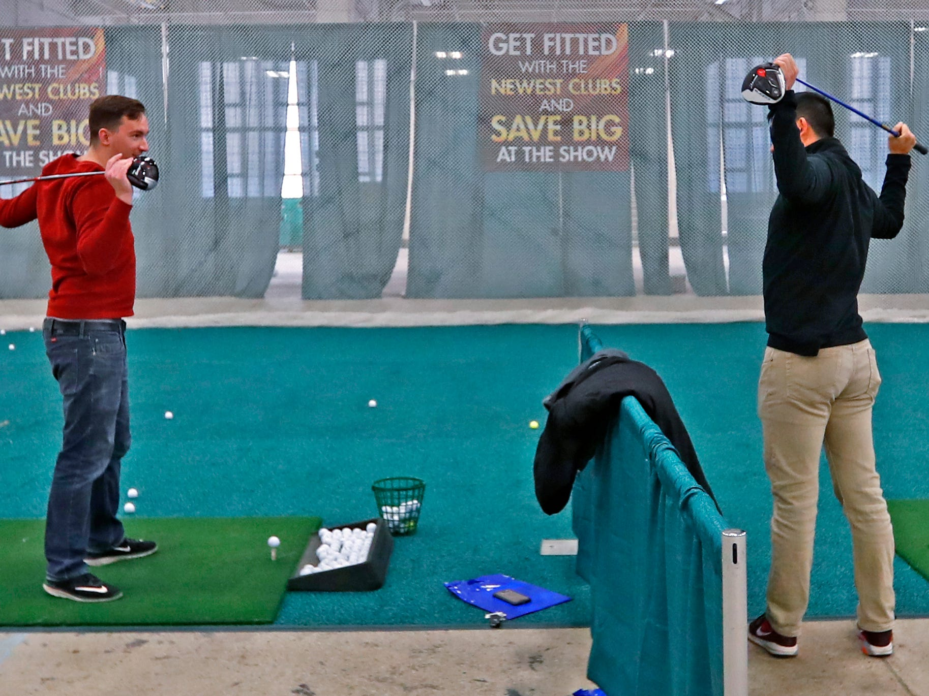 Sam Richmond, left, and Scott Wong warm up to try out clubs at the Club Champion booth during the Indy Golf Expo at the Indiana State Fairgrounds, Sunday, Jan. 20, 2019.