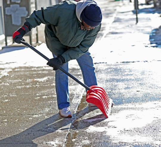 John Edwards scrapes ice off the sidewalk in front of the at Chez Napoleon Apartments, Sunday, Jan. 20, 2019.