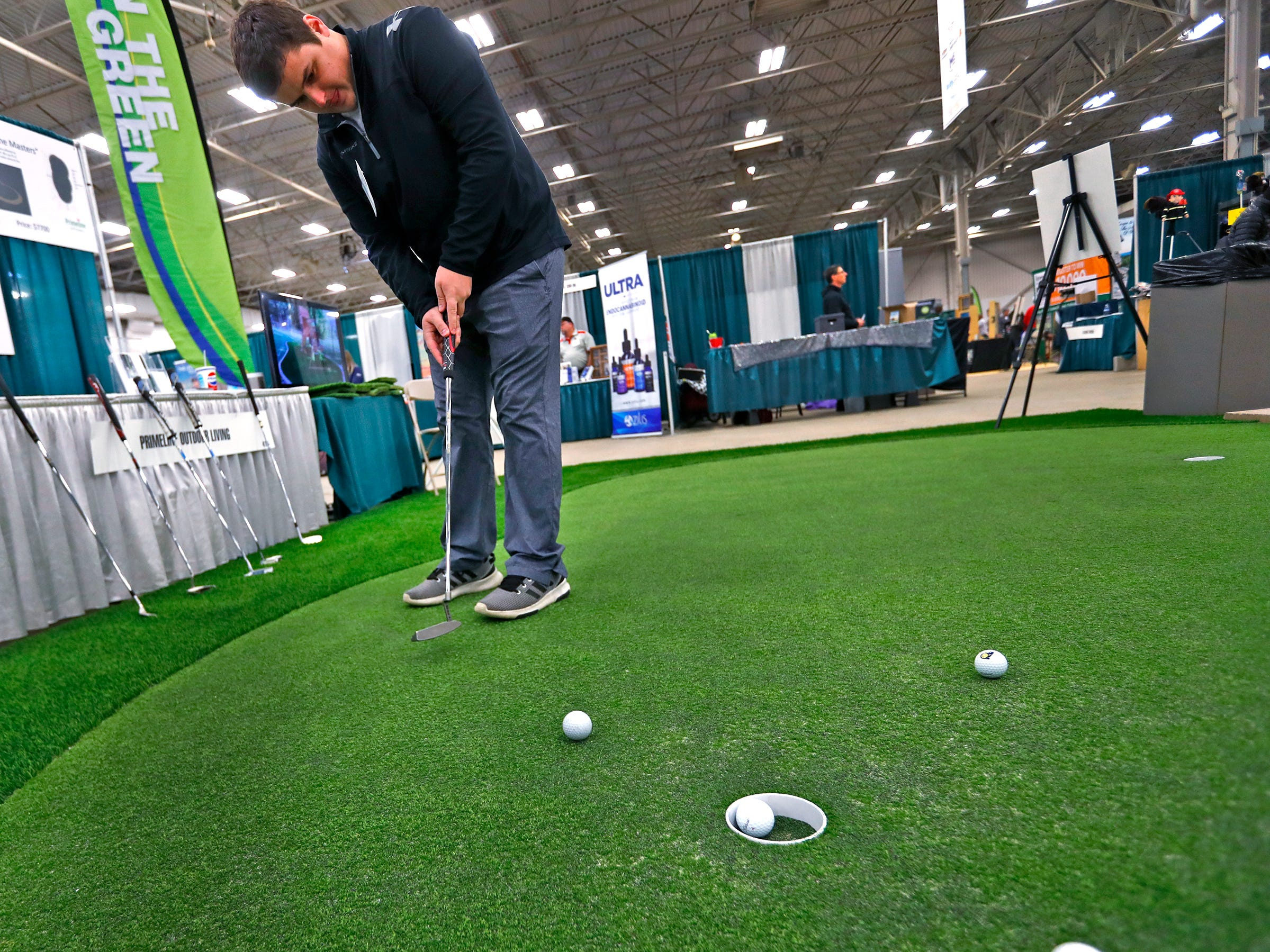 Joe Buhle, with Primeline Outdoor Living, sinks putts in between helping customers during the Indy Golf Expo at the Indiana State Fairgrounds, Sunday, Jan. 20, 2019.