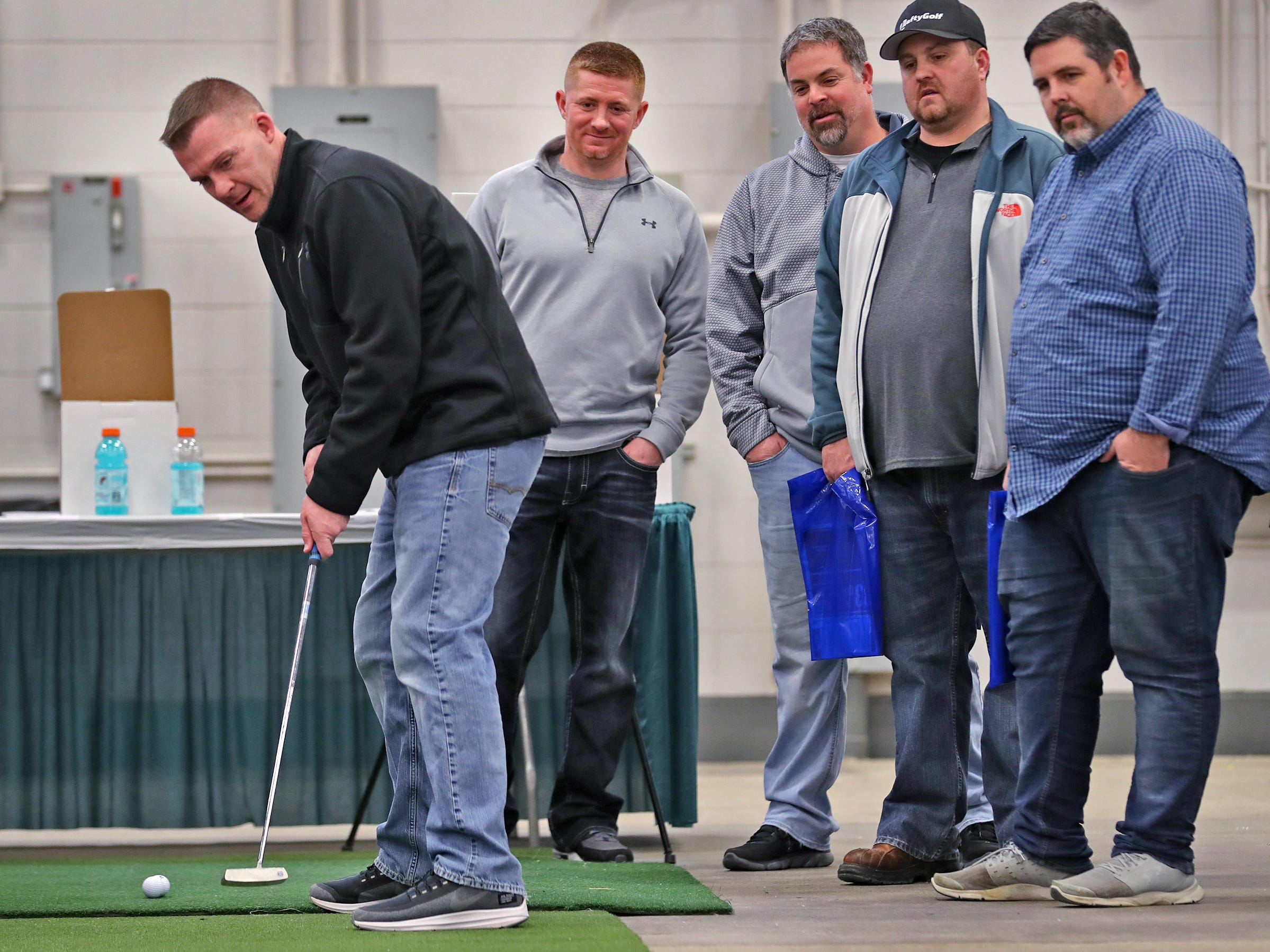 Dusty Massengale, left, tries his hand at putting as friends watch closely, during the Indy Golf Expo at the Indiana State Fairgrounds, Sunday, Jan. 20, 2019.