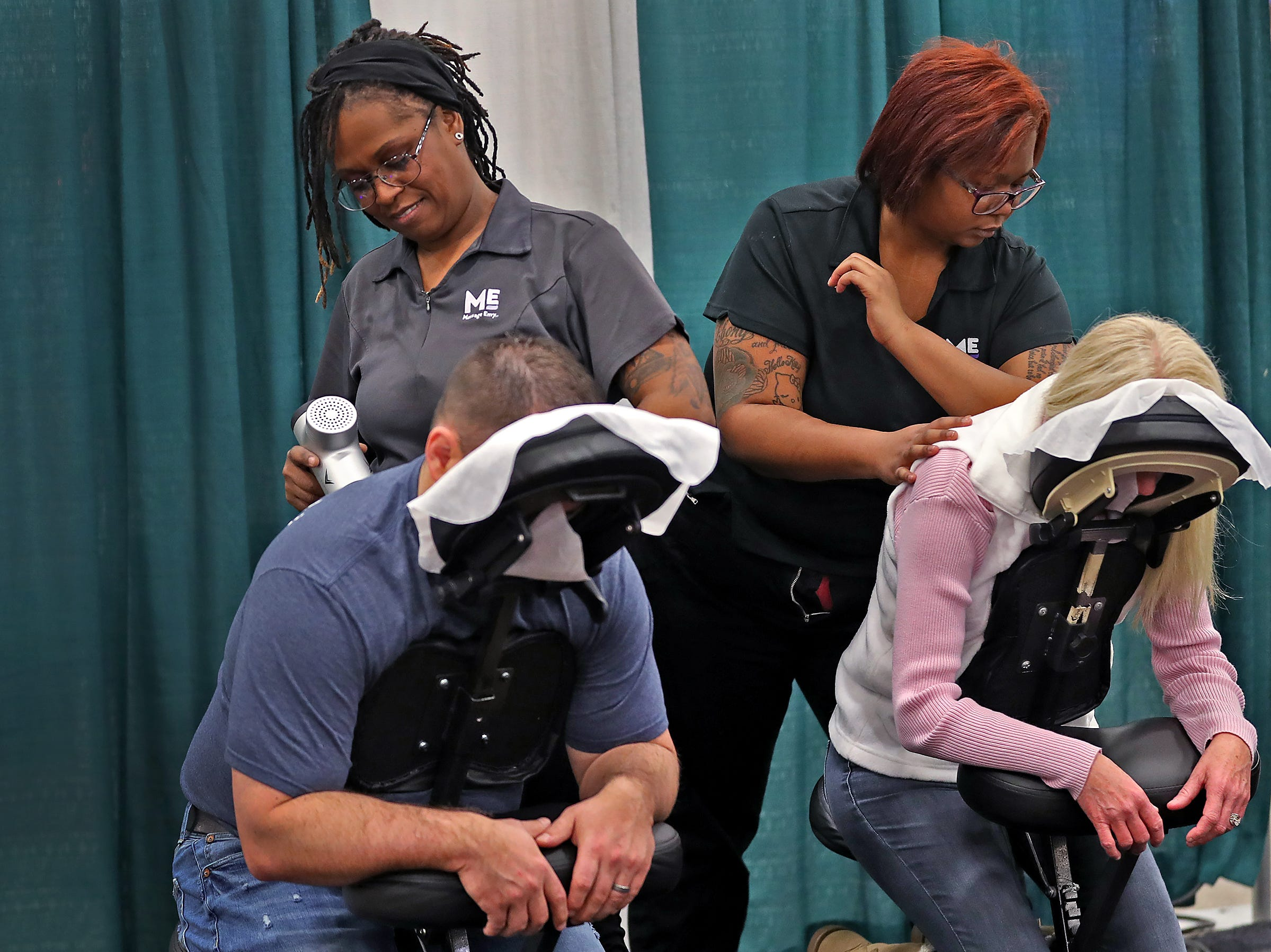 John Chladny gets massaged by Shyra Cobb, left, and Sheryl Messer is massaged by Ebony Greenwade, right, at the Massage Envy booth, during the Indy Golf Expo at the Indiana State Fairgrounds, Sunday, Jan. 20, 2019.  The company did chair and stretching massages but also offered advice on how to stretch to strengthen one's golf game.