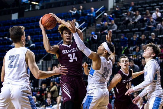 Oskaloosa's Xavier Foster (34) gets fouled by Cedar Rapids Jefferson's Willie Guy III (21) during a boys' basketball game in the Wells Fargo Advisors Shootout on Saturday, Jan. 19, 2019, at the U.S. Cellular Center in Cedar Rapids, Iowa.