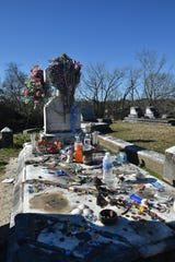 The grave of Kelly Mitchell, Queen of the Gypsies, is covered in beads, coins and other gifts left by visitors who have been visiting her grave for 104 years.