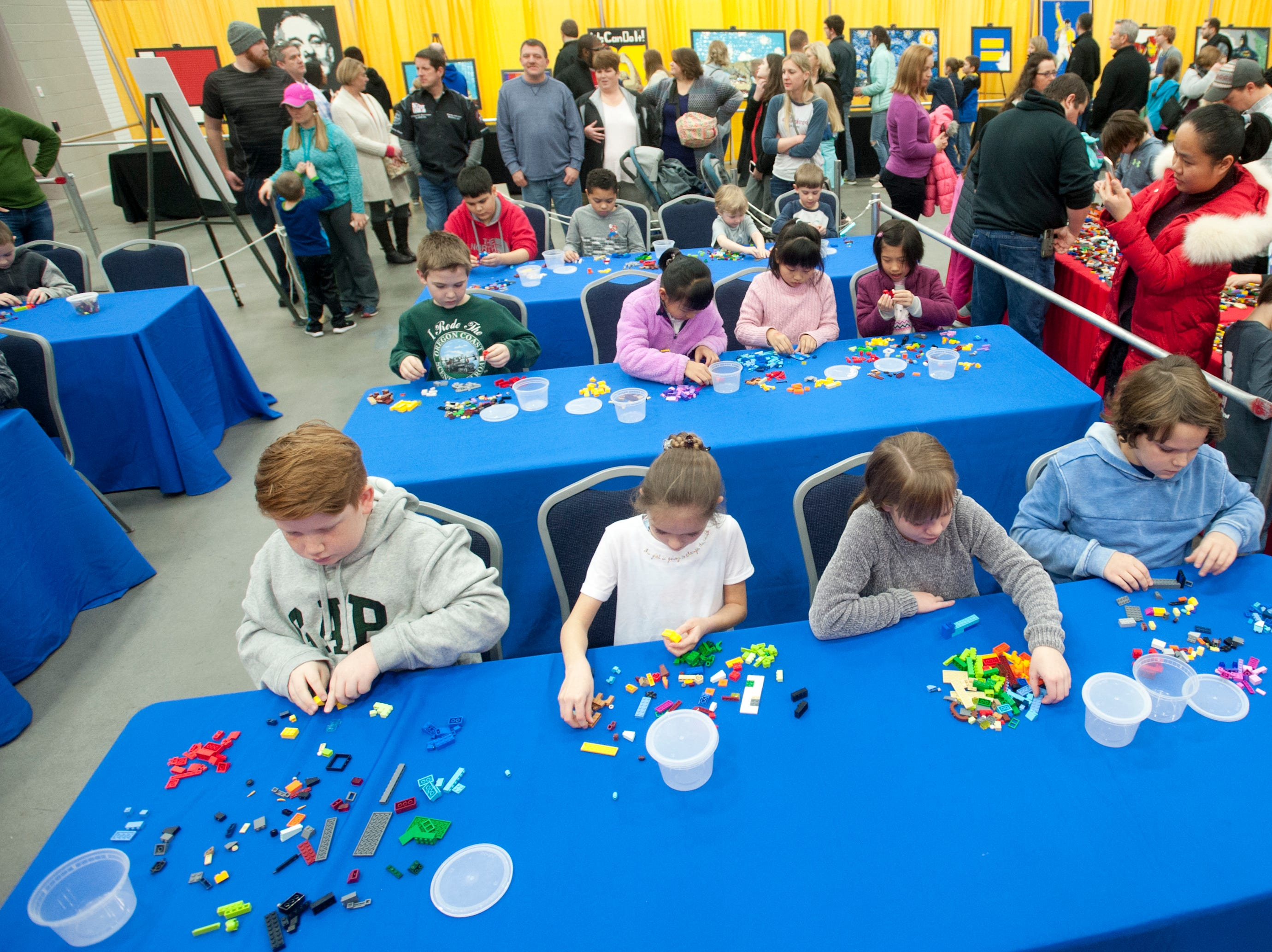 During a Lego building competition, l-r: Sam Catron, 11, of Shelbyville, Kinsley Mast, 8, of Mountain View, Ark., Petra Hawkins, 9, of Danville and anded Hawkins, 10, her brother: all try their hand at creating a space station at the BrickUniverse Lego Fan Convention at the Kentucky International Convention Center in downtown Louisville.19 January 2019