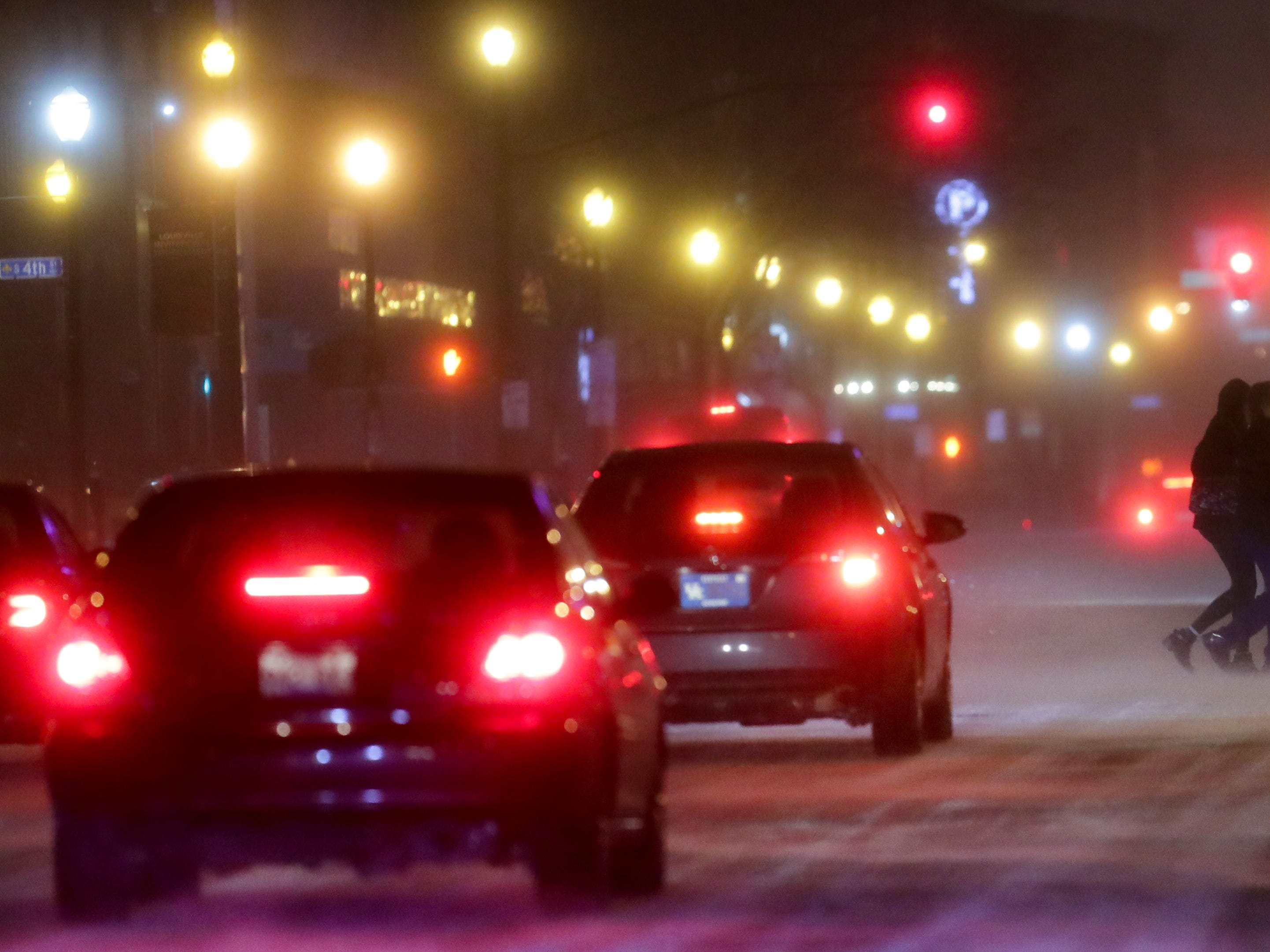 Traffic and pedestrians dealt with the winter storm as it hit downtown Louisville Saturday night. 