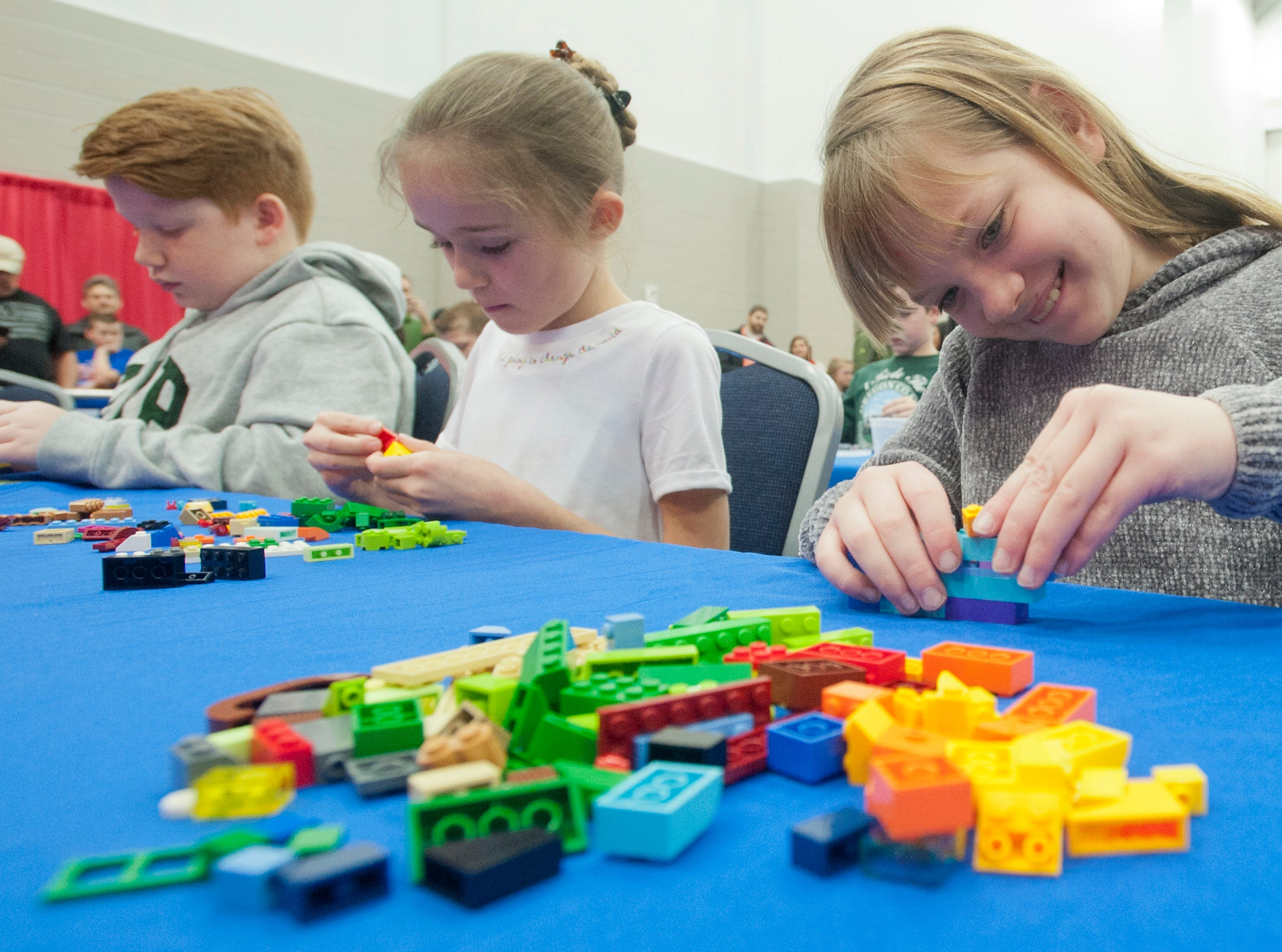 During a Lego building competition, l-r: Sam Catron, 11, of Shelbyville, Kinsley Mast, 8, of Mountain View, Ark. and Petra Hawkins, 9, of Danvilleall try their hand at creating a space station at the BrickUniverse Lego Fan Convention at the Kentucky International Convention Center in downtown Louisville.19 January 2019