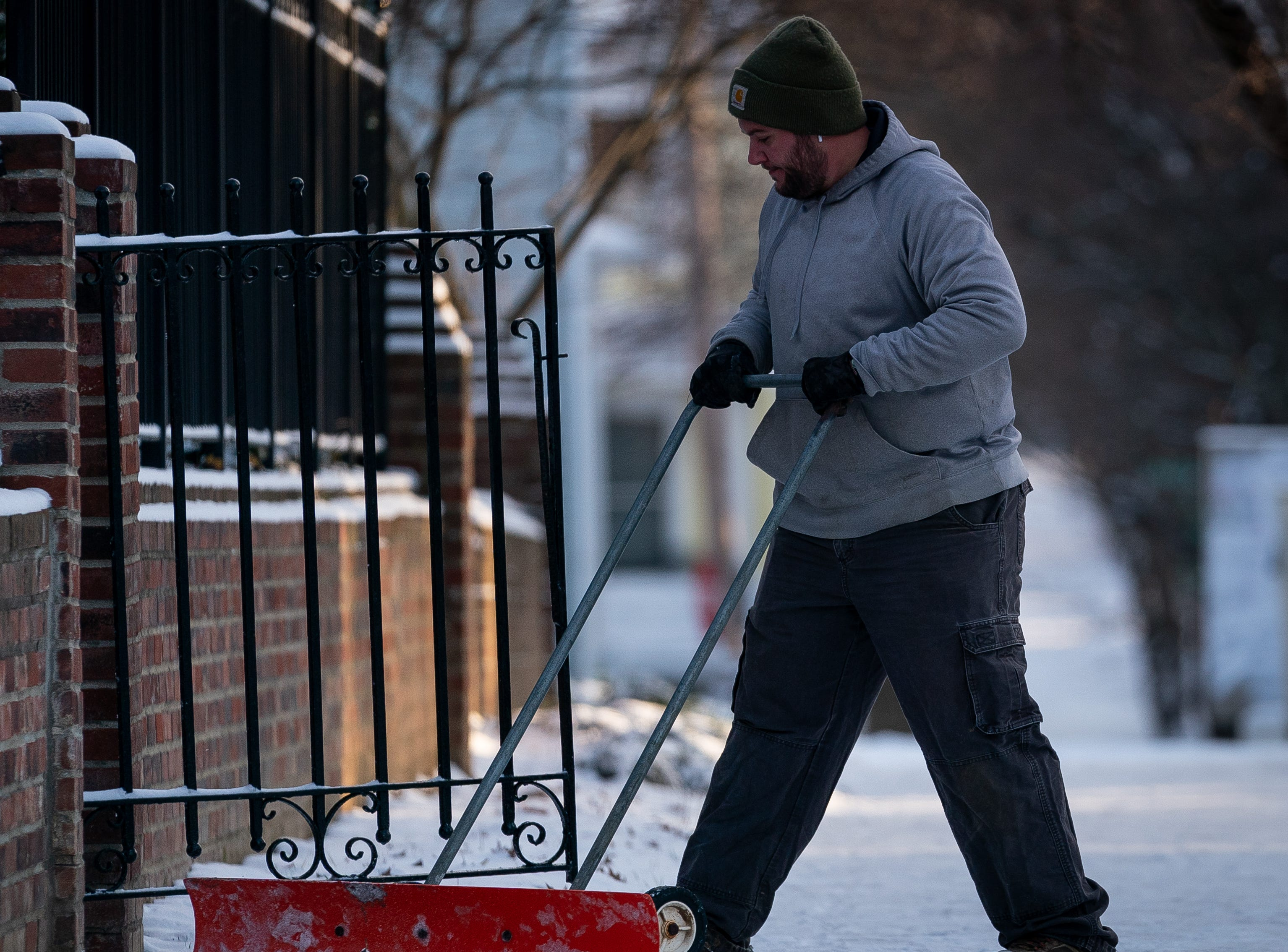 Kyle England shovels snow in the Highlands following a snow storm that dusted Louisville, Ky., Sunday, Jan 20, 2019.