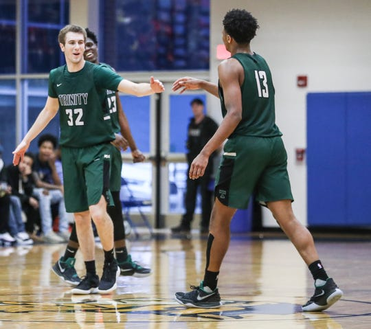 Trinity's Stan Turnier reaches out to teammate David Johnson as the Shamrocks secured its sixth LIT title since 2005.