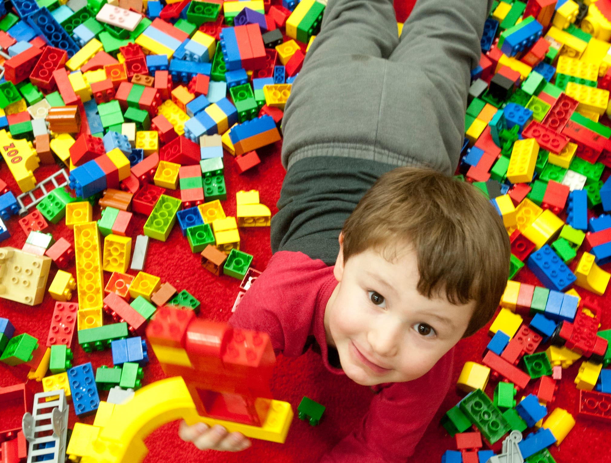 Levi Cook, age 4, of Mt. Washington, shows off his large Legos creation as he lays amid the pieces at the BrickUniverse Lego Fan Convention at the Kentucky International Convention Center in downtown Louisville.19 January 2019