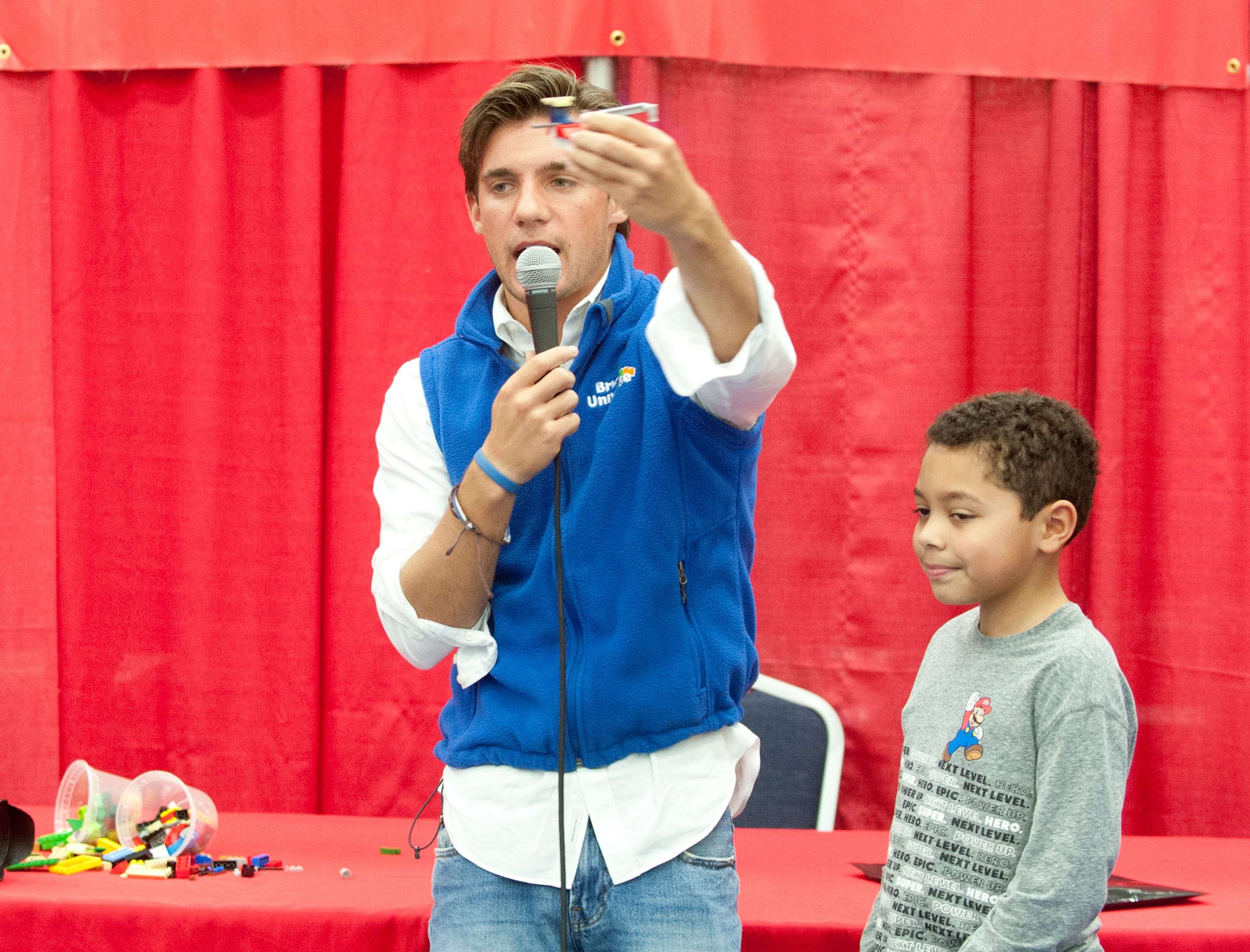 During a Lego building competition Challenge Zone host and judge Roland Beights holds up the winner of a competition to build the best space station as the station's creator, Luke Johnson, age 8, of Buckner stands to his right.19 January 2019