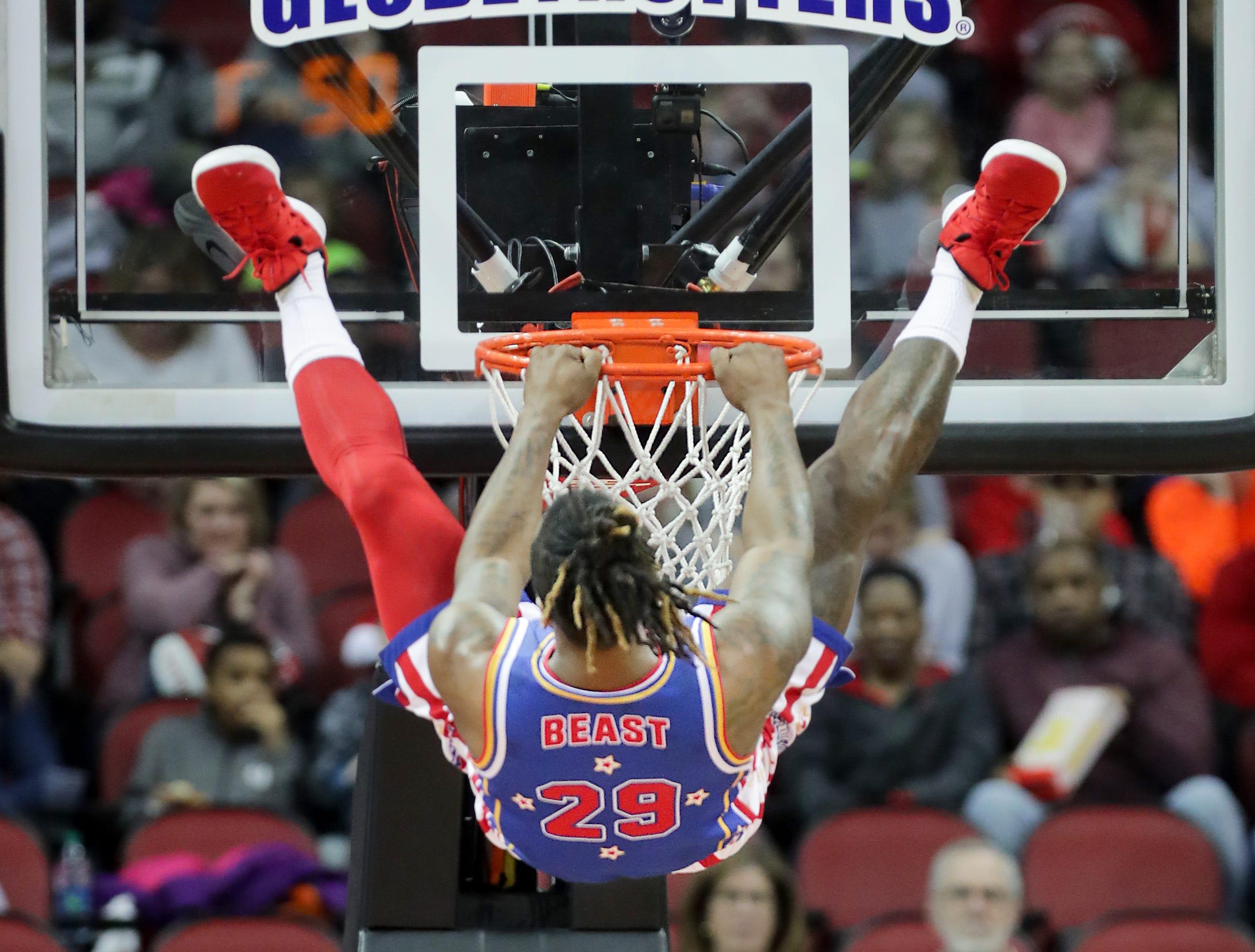 Harlem Globetrotters' Beast hangs on the rim after a slam dunk. Jan. 19, 2019