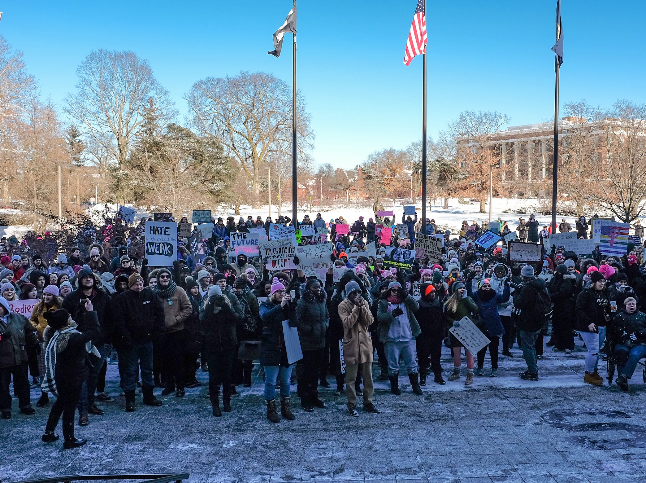 People in Lansing's Women's March chant and cheer in front of the MSU Administration Building as they wait for the speakers to start Sunday, Jan. 20, 2019.