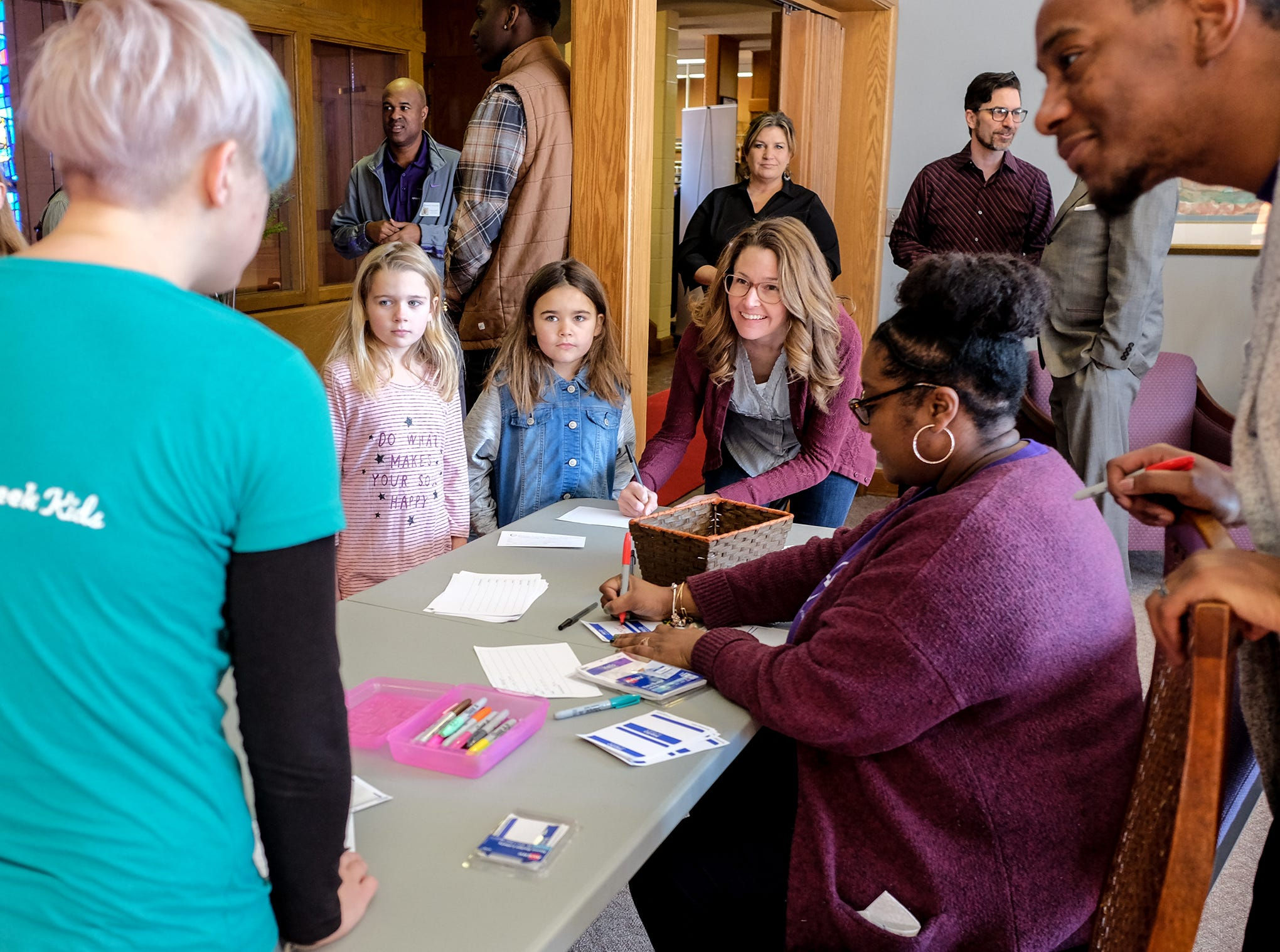 Kendra Byrd, sitting, registers youngsters from Sycamore Creek Church for child care before services at Epicenter of Worship Church Sunday, Jan. 20, 2019.