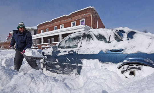 Ali Grose of Mansfield digs his vehicle out of the snow Sunday afternoon. Grose said he just wanted to move his car so his side of the road could be cleared on Fourth Street.
