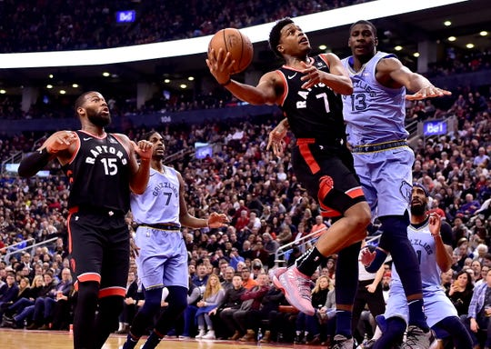 Toronto Raptors guard Kyle Lowry (7) drives to the net as teammate Greg Monroe (15), Memphis Grizzlies forward Jaren Jackson Jr. (13) and his teammate Justin Holiday (7) look on during during the first half of an NBA basketball game in Toronto on Saturday, Jan. 19, 2019. (Frank Gunn/The Canadian Press via AP)