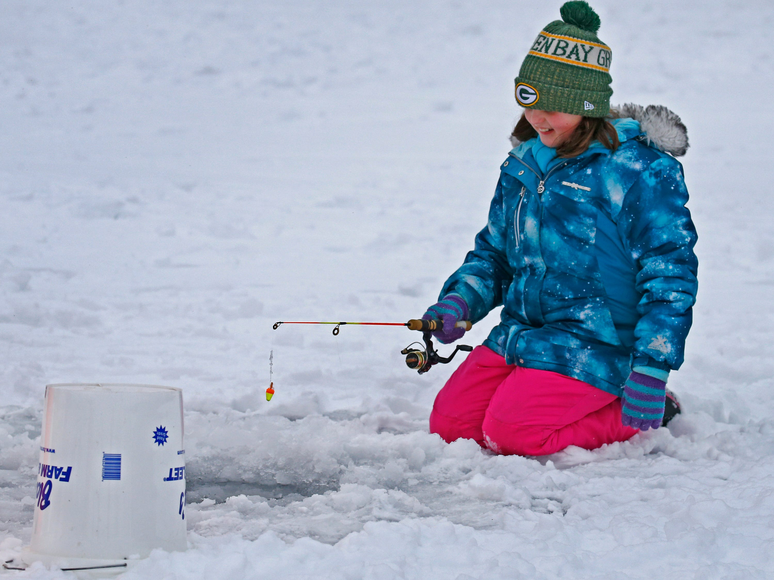 Stellah Freitag of Watertown tried using a jig pole on Lower Genesee Lake in Summit during a free instructional ice fishing day hosted by Sons of the Watertown American Legion Post 189 on Jan. 19. The event drew more than 50 children and their attending adults.