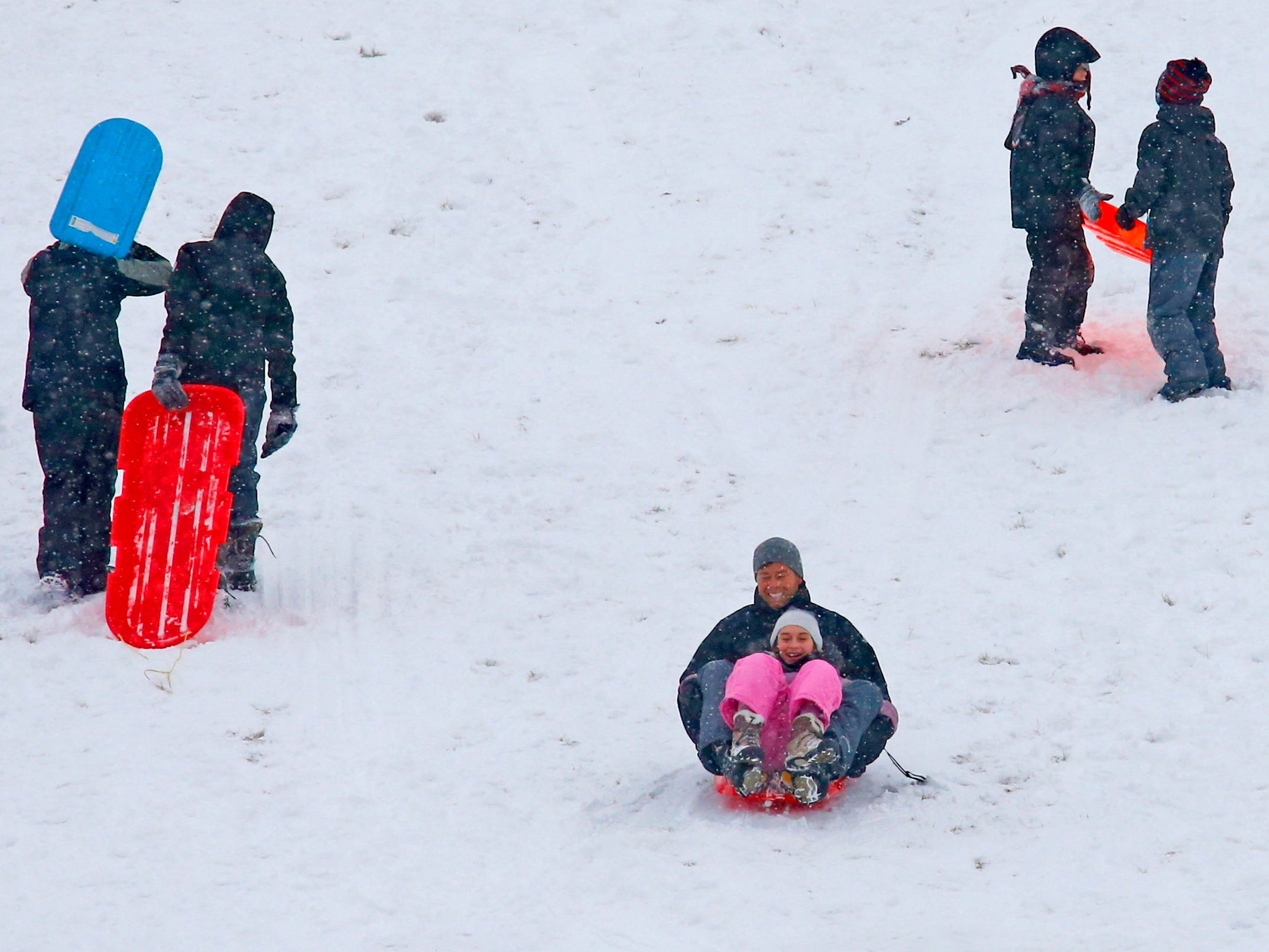 Sledders glide on the Wirth Park South hill in Brookfield after the first sledding snow arrived overnight on Jan. 19.