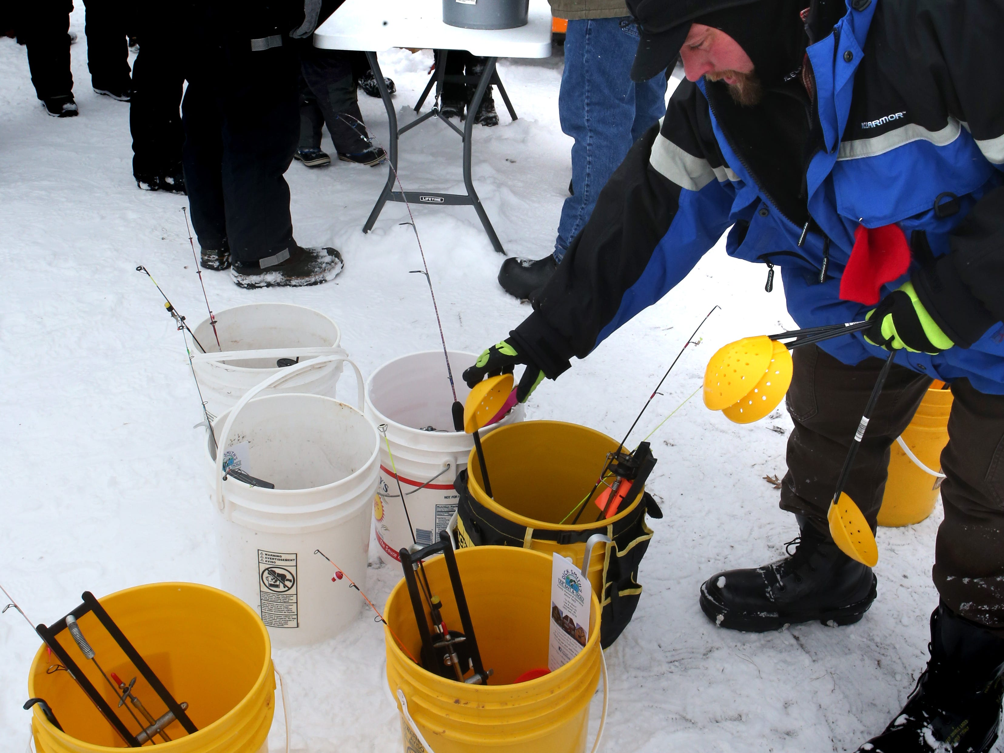 Tony Dittmann sets up buckets containing a tip up and jig poles to be loaned to families to try ice fishing on Lower Genesee Lake in Summit during a free instructional ice fishing day hosted by Sons of the Watertown American Legion Post 189 on Jan. 19. The event drew more than 50 children and their attending adults.