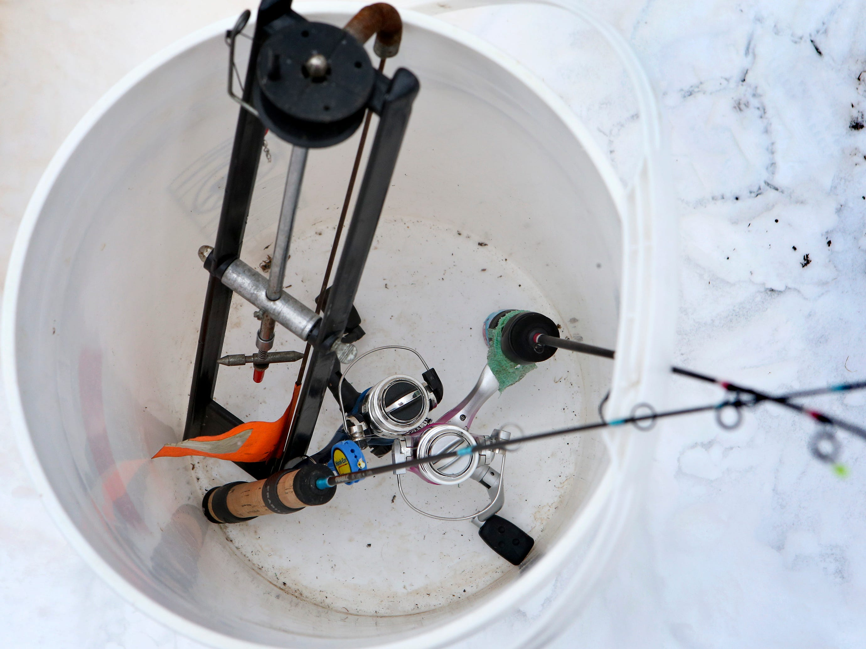 Buckets containing a tip up and jig poles are loaned to families to try ice fishing on Lower Genesee Lake in Summit during a free instructional ice fishing day hosted by Sons of the Watertown American Legion Post 189 on Jan. 19. The event drew more than 50 children and their attending adults.
