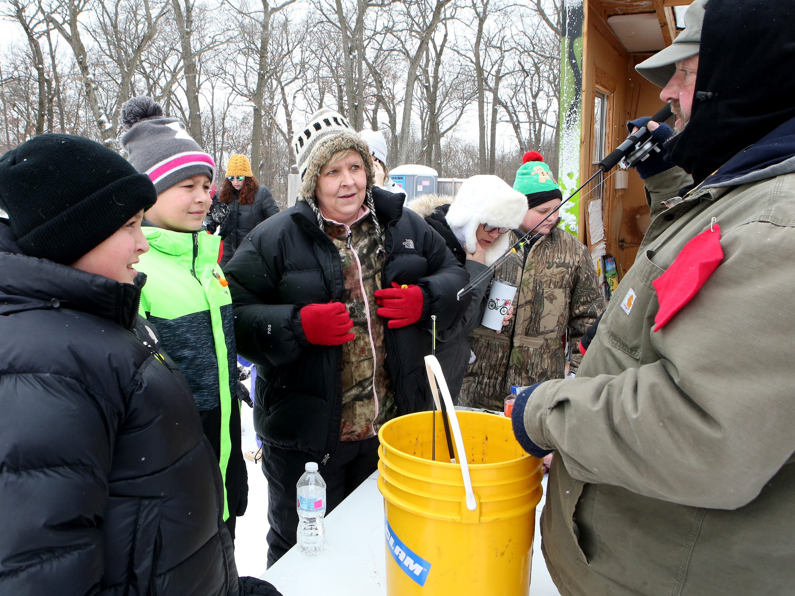 Anthony Chentis shows Austin (left), Landon and Jennifer Garcia of Dousman some ice fishing basics as he loans out a bucket of ice fishing gear on Lower Genesee Lake in Summit during a free instructional ice fishing day hosted by Sons of the Watertown American Legion Post 189 on Jan. 19. The event drew more than 50 children and their attending adults.