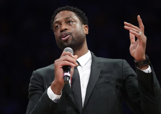 Former Marquette men's basketball standout and NBA star Dwyane Wade speaks as he is honored at halftime of the MU game on Sunday.