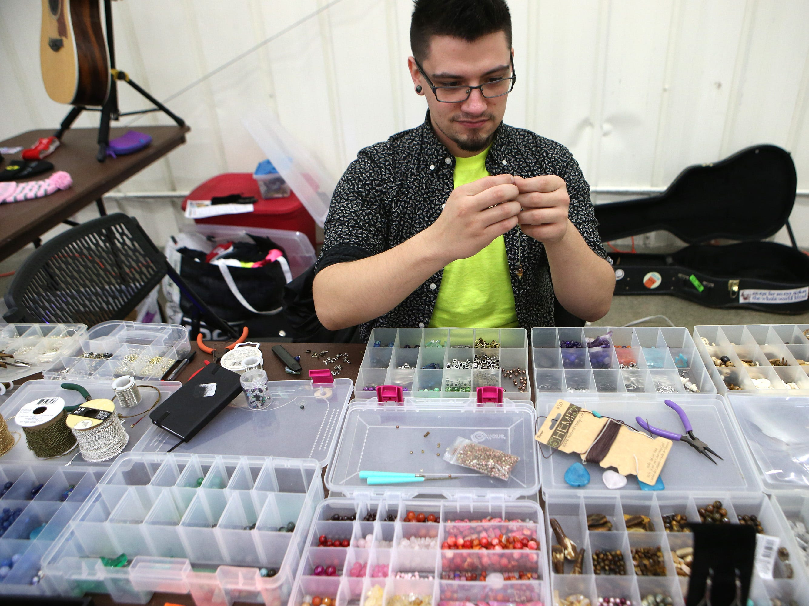 Joey Stone of Waukesha creates jewelry using guitar strings during business winter vendor event hosted by Beer Me. Waukee, a beer-inspired Milwaukee apparel brand, at the Waukesha County Expo Center on Jan. 19.