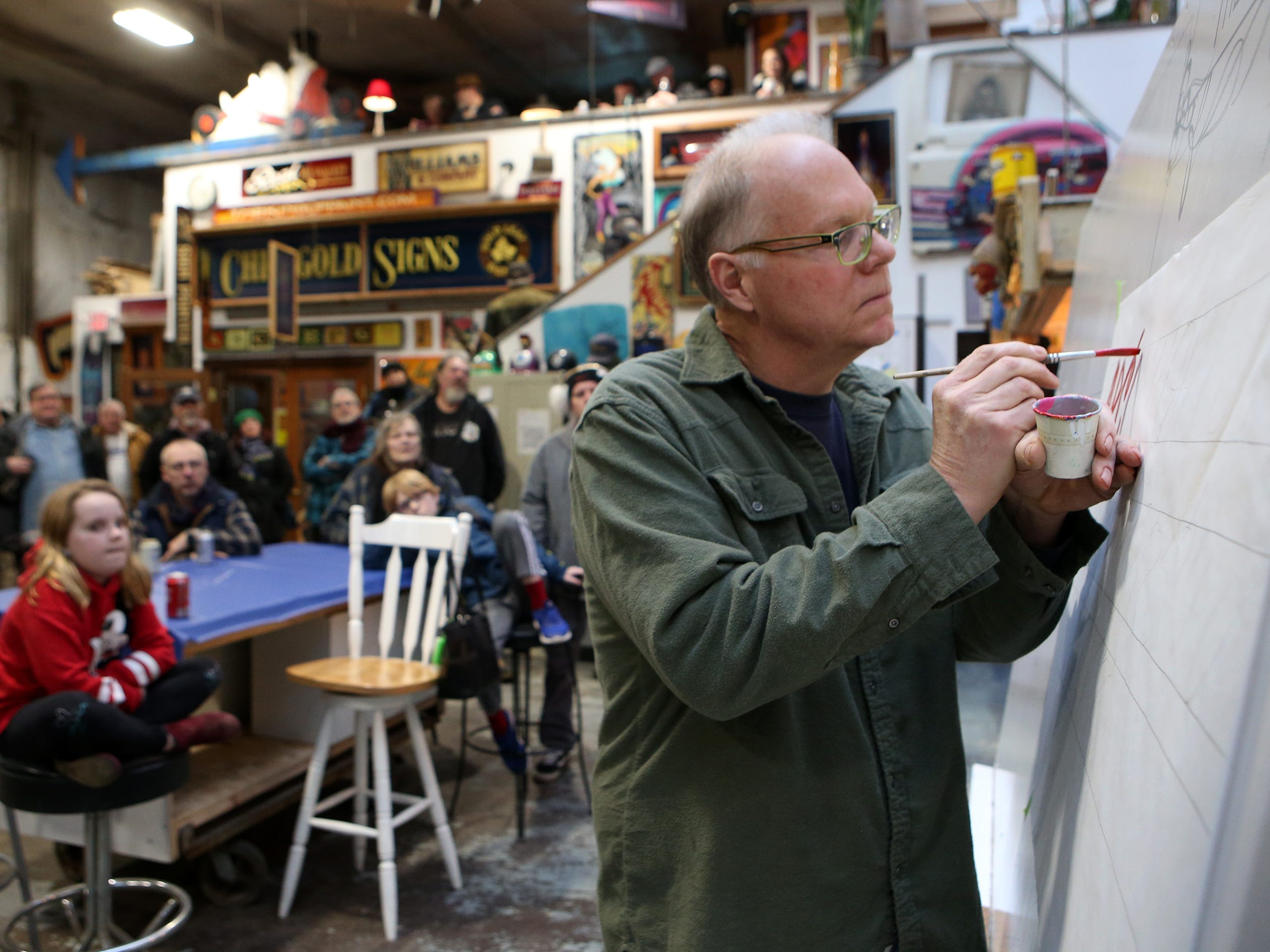 Jeff Williams, sign painter and owner of The King of Paint, demonstrates freehand lettering during an open house at the King of Paint shop in St. Francis on Jan. 19.
