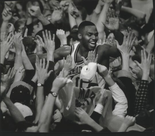Marquette senior Tony Miller is carried by the Arena crowd after helping his team defeat South Florida, 57-50, in 1995.