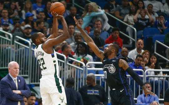 Khris Middleton of the Bucks hoists up an outside shot over Magic forward Jonathan Simmons during the first quarter on Saturday night.