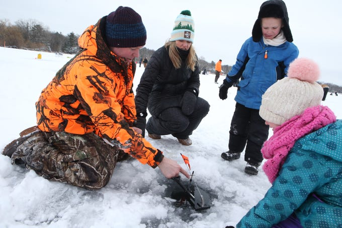 Kevin Healy shows Amber and Jack Healy how a tip up ice fishing rig works on Lower Genesee Lake in Summit during a free instructional ice fishing day hosted by Sons of the Watertown American Legion Post 189 on Jan. 19. The event drew more than 50 children and their attending adults.