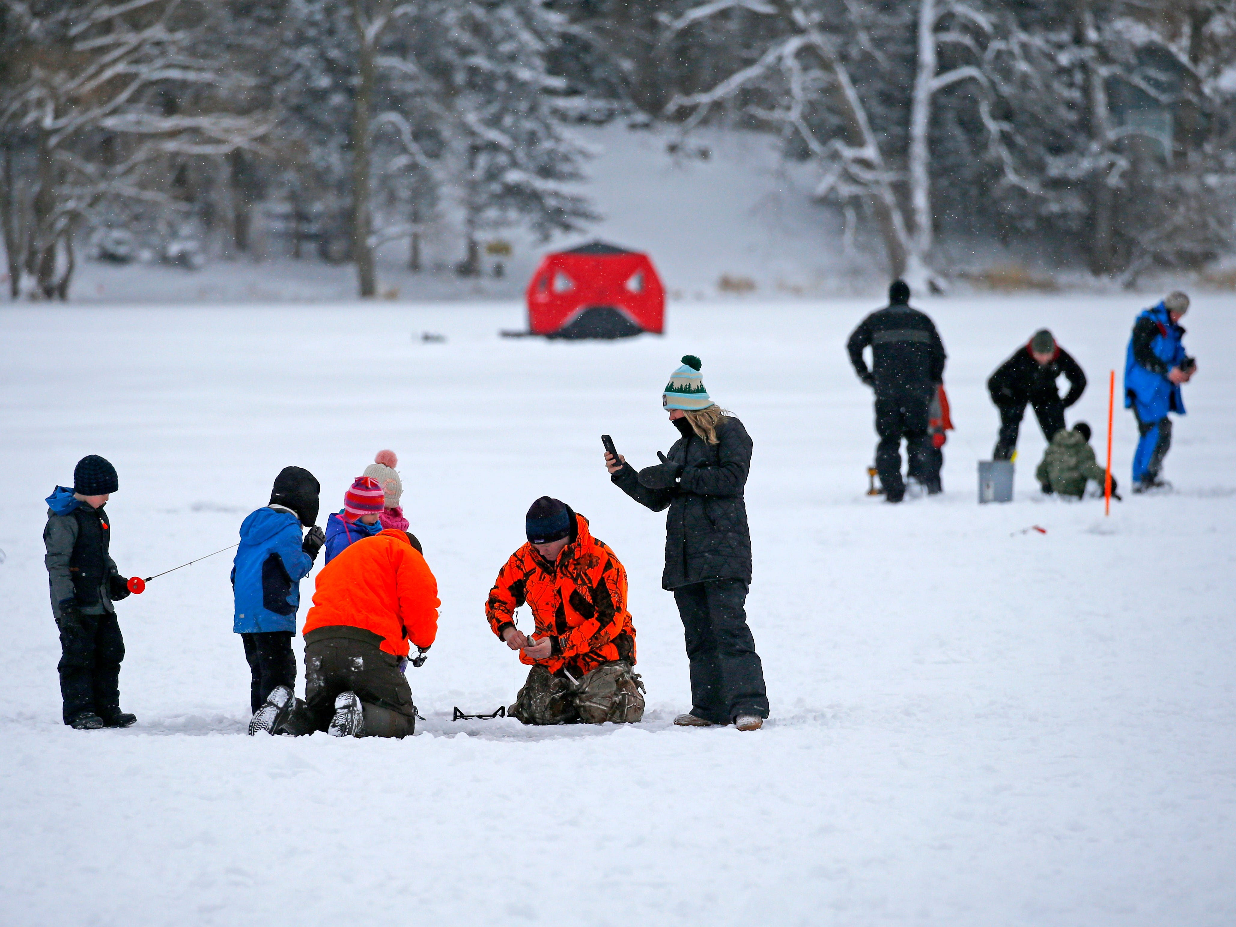 Families try ice fishing on Lower Genesee Lake in Summit during a free instructional ice fishing day hosted by Sons of the Watertown American Legion Post 189 on Jan. 19. The event drew more than 50 children and their attending adults.