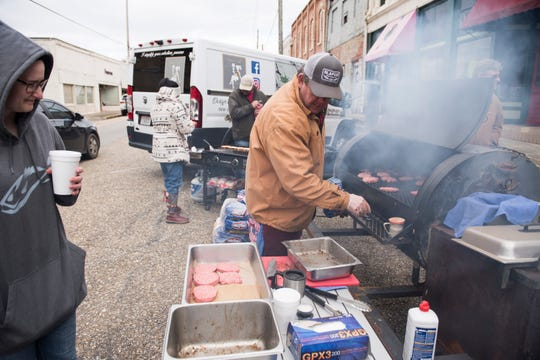 Volunteers cook up hamburgers to be distributed to first responders and volunteers in Wetumpka, Ala., on Sunday, Jan. 20, 2019.