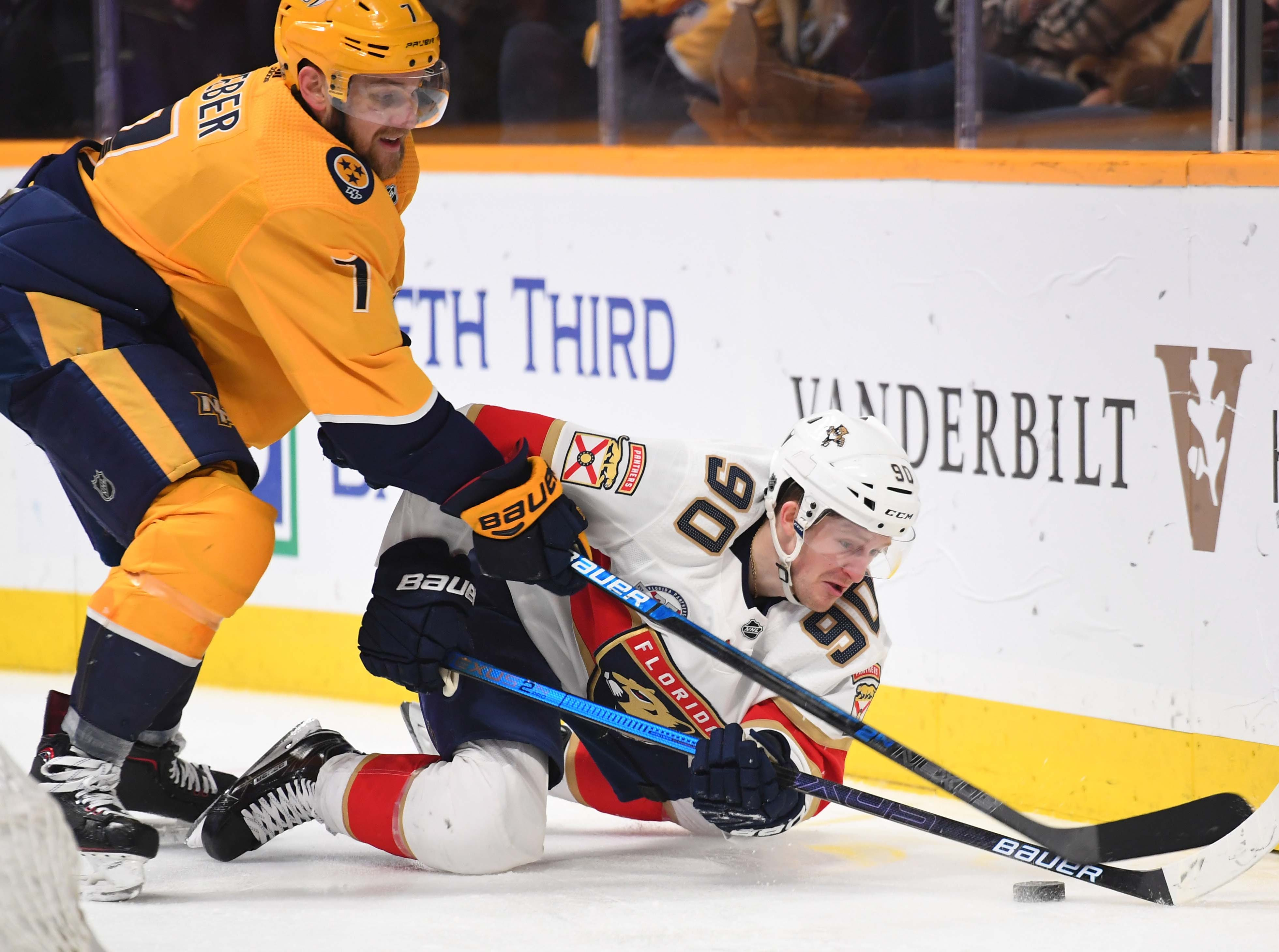 Florida Panthers center Jared McCann (90) works against Nashville Predators defenseman Yannick Weber (7) after drawing a tripping penalty during the second period at Bridgestone Arena.