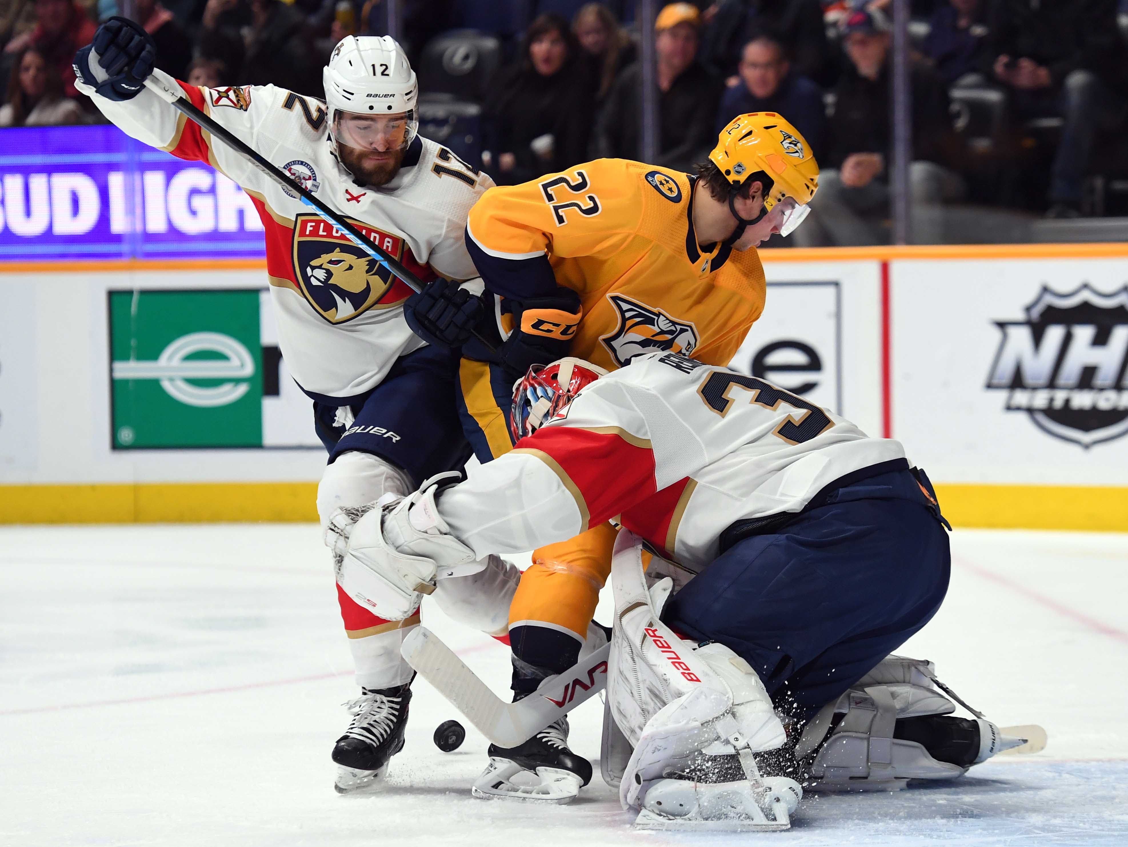 Nashville Predators left wing Kevin Fiala (22) works against Florida Panthers defenseman Ian McCoshen (12) to get a shot on Florida Panthers goaltender James Reimer (34) during the first period at Bridgestone Arena.