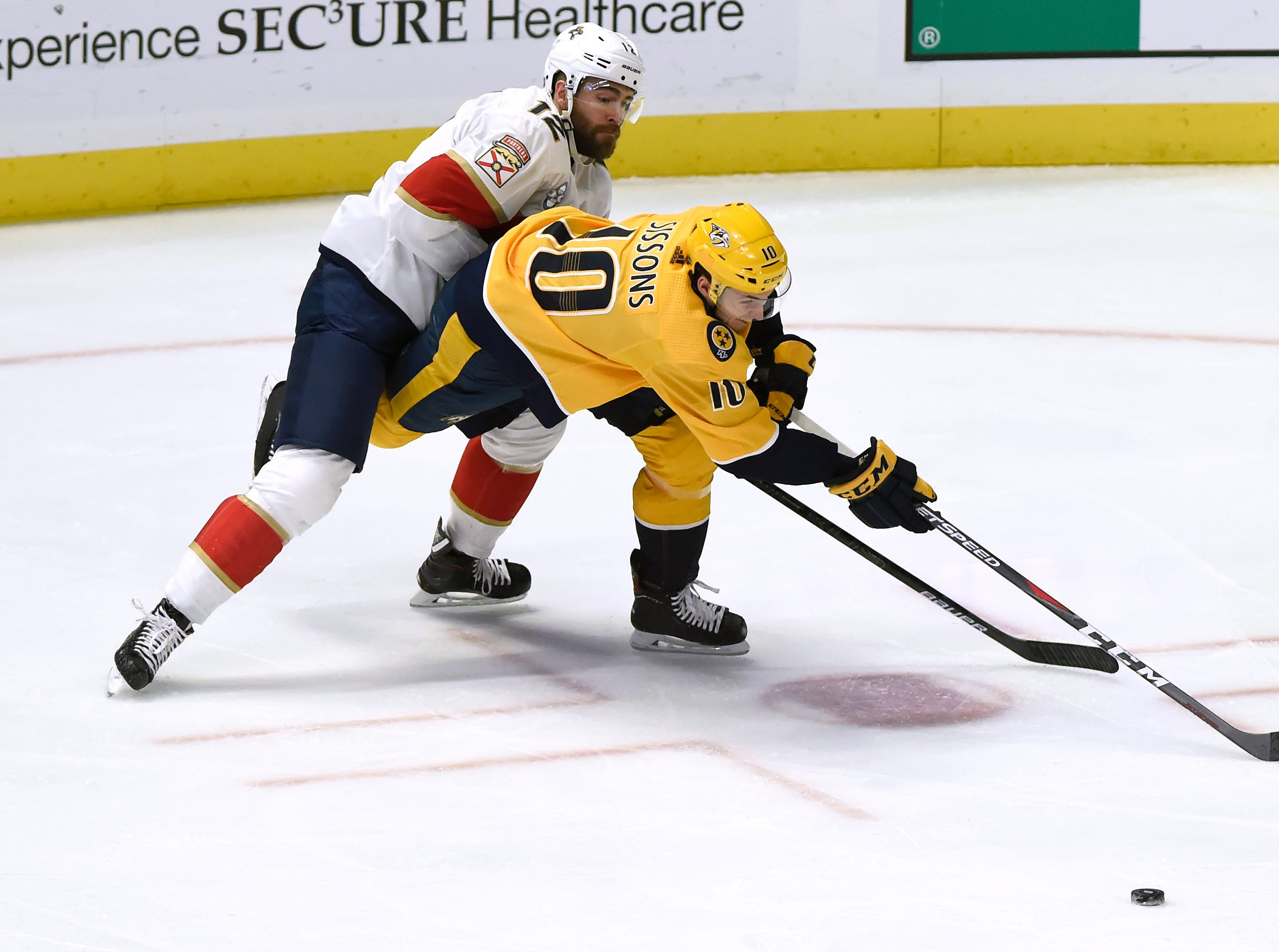 Nashville Predators center Colton Sissons (10) and Florida Panthers defenseman Ian McCoshen (12) chase the puck during the first period of an NHL hockey game Saturday, Jan. 19, 2019, in Nashville, Tenn.