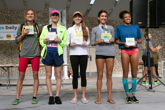 First-place women's category winner Lindsey Scherf, left,  joins the podium with the top women finishers at the conclusion of the Naples Daily News Half Marathon participants Sunday.
