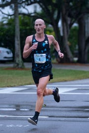 Tyler McCandless makes his way to the finish line to win the Naples Daily News Half Marathon, Sunday, Jan. 20, 2019, in Naples.