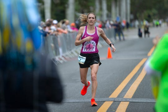 Stephanie Pezzullo crosses the finish line in the Naples Daily News Half Marathon on Sunday. Pezzullo finished second in the race.