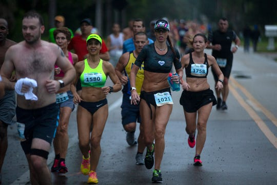 Participants in the Naples Daily News Half Marathon make their way up Gordon Drive on Sunday.