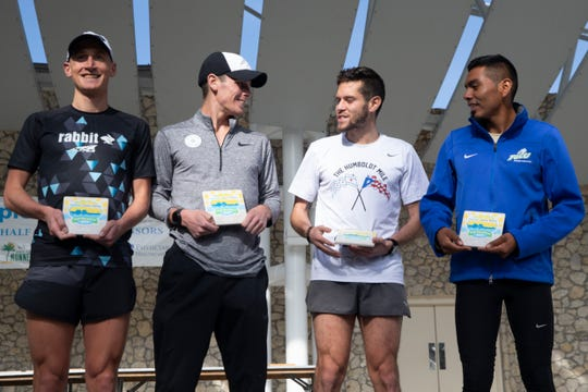 Top men's Naples Daily News Half Marathon winners pose for photos on the podium, Sunday, Jan. 20, 2019, in Naples.